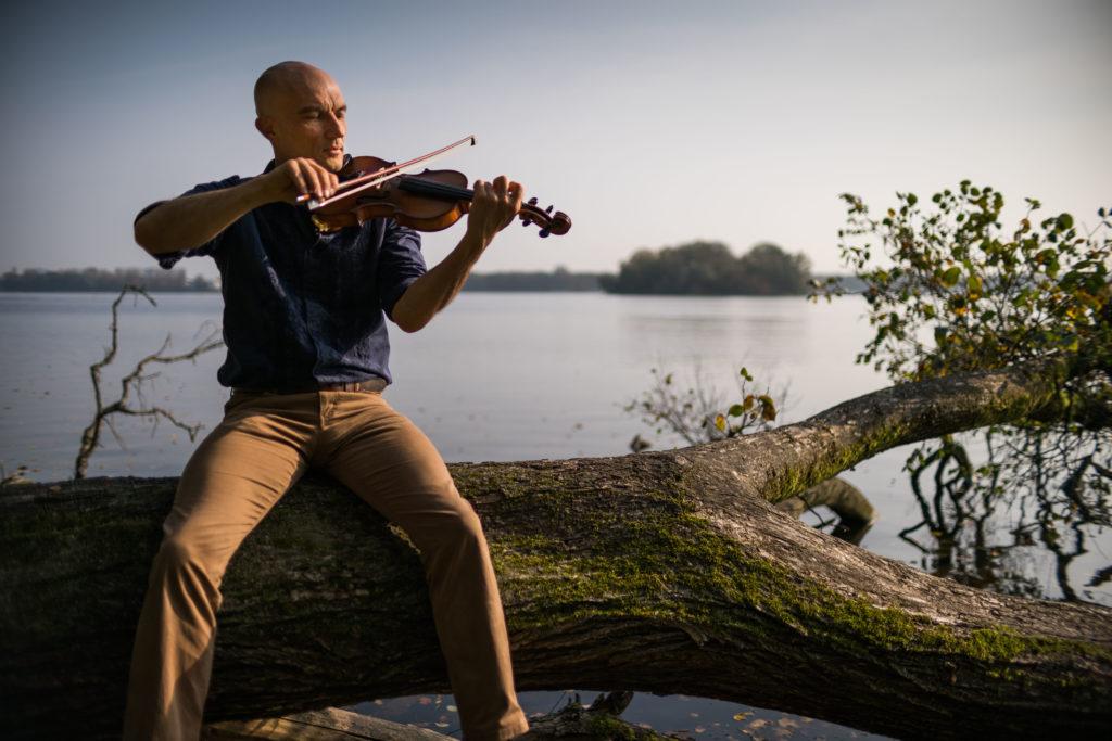 Miroslav mit Geige am See